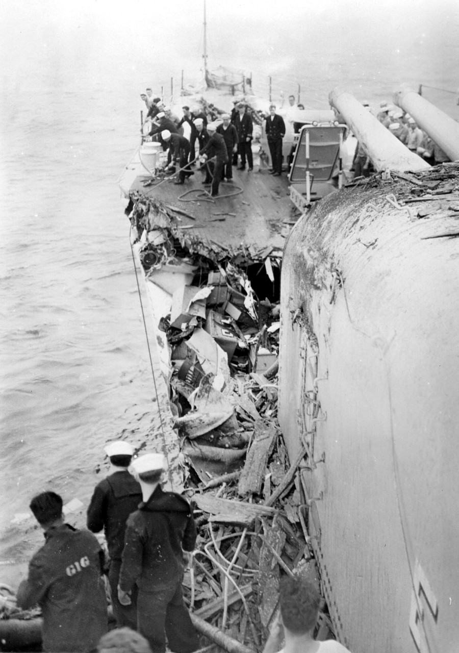 Damage control in the wake of the collision with Silverpalm. Note the extent of the tangled wreckage on the port side, amidst which one can identify a chair that was apparently in one of the obliterated staterooms. Sailor at left foreground was apparently assigned to the captain's gig; also note officers and enlisted men looking on from the forecastle.  (U.S. Navy Photograph, National Archives and Records Administration, Still Pictures Branch, College Park, Md.)