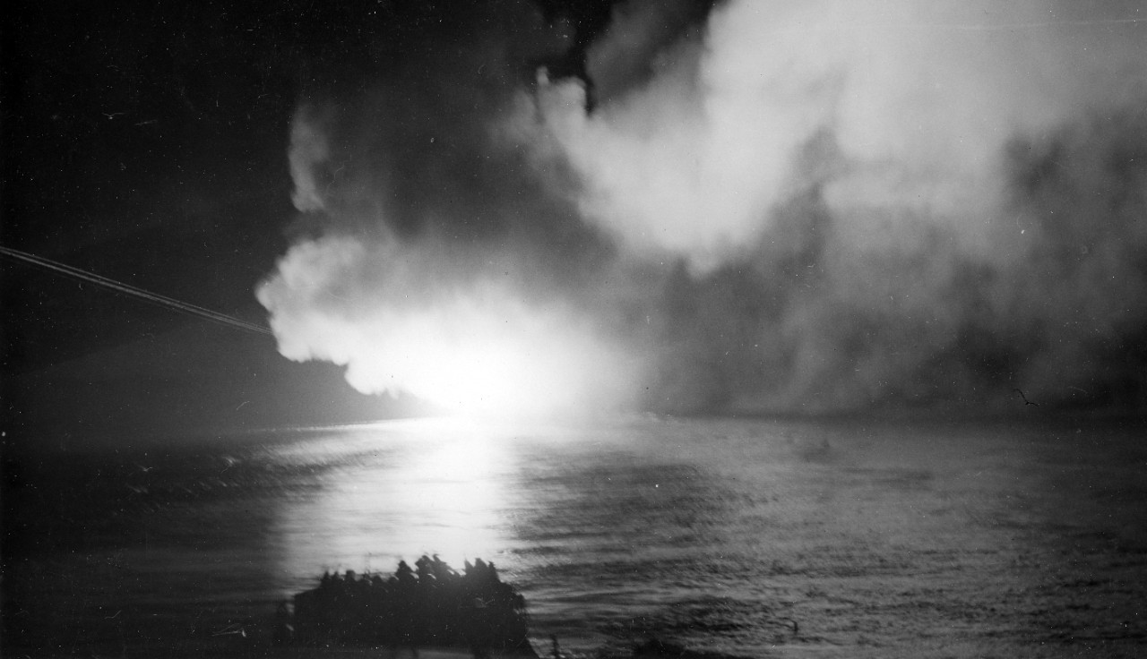 Completely enveloped with smoke from her own gunfire, Cleveland bombards targets on northern Bougainville Island on 24 December 1943 (as seen from her sister ship Columbia (CL-56)). Note the bright streaks on the left tracing the trajectory of a salvo from her main battery. (U.S. Navy Photograph 80-G-299036, National Archives and Records Administration, Still Pictures Branch, College Park, Md.)
