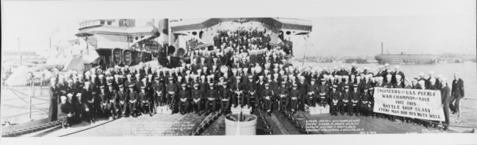"A panoramic photograph of Pueblo's Engineering Crewmen, taken on her forecastle at Norfolk, Va., 3 December 1918. Note the banner proclaiming: ""Engineers of U.S.S. Pueblo...War Champion of Navy...1917–1918...Battle Ship Class...Every man did his job well"". The ship alongside, at left, is probably Huron (Armored Cruiser No. 9). She is still painted in pattern camouflage. Receiving ship Richmond is in the right distance. Photographed by the G.L. Hall Optical Co., of Norfolk."