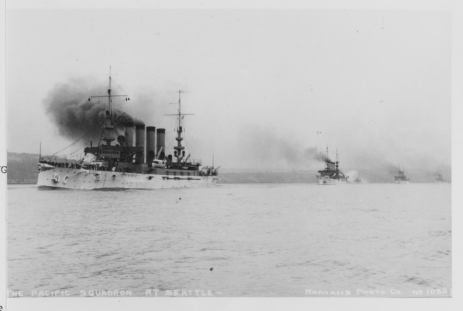 "Pennsylvania (Armored Cruiser No. 4) or Colorado lead a column of four armored cruisers into Puget Sound toward Seattle, Wash. Photograph taken circa 1907–1908 and published on a postal card by Rodman's ""Real Photo"" Post Cards, sold by Hopf Brothers Co., Seattle, and postmarked at Seattle on 25 May 1908. (Courtesy of H.E. Coffer, 1986, U.S. Navy Photograph NH 101604, Photographic Section, Naval History and Heritage Command)"