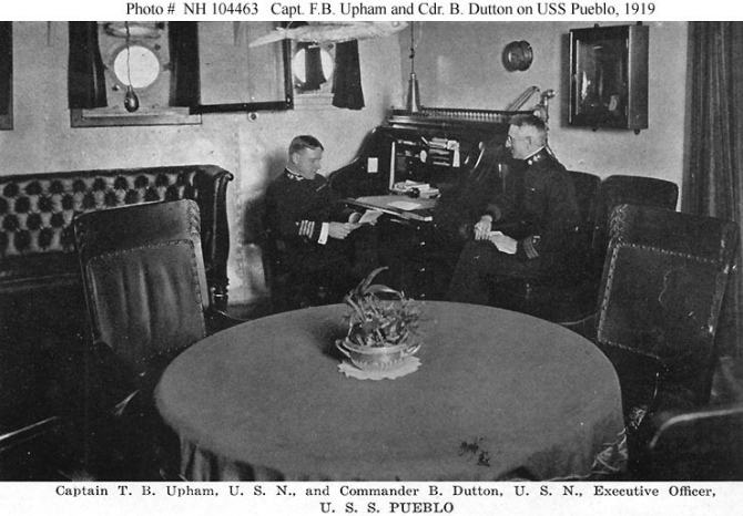 Halftone reproduction of a photograph, taken circa 1919, of Capt. Upham (left) at his desk, with Cmdr. Benjamin Dutton, the executive officer, at right. One of the ten images from the Souvenir Folder. (Donation of Dr. Mark Kulikowski, 2007, U.S. Navy Photograph NH 104463, Photographic Section, Naval History and Heritage Command)