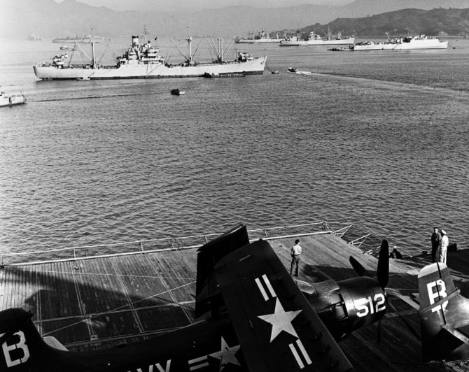 U.S. Navy ships take on supplies while moored in Sasebo harbor, circa December 1950. The photograph was taken from Princeton (CV-37). Among the ships in the background are Mount Katmai (AE-16), in left center, and Comstock, at right. Aircraft on Princeton's deck are Douglas AD-4 Skyraiders. (U.S. Navy Photograph, National Archives Still Pictures Branch, 80-G-423620).
