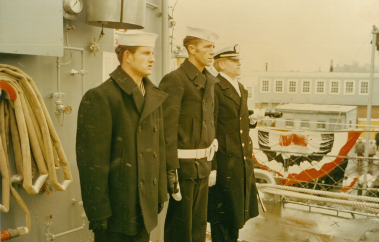 As a tribute to both the ship and its namesake, Cook's first watch consisted of (L to R) Seaman Thomas M. Cook (Messenger), Commissaryman First Class Clarence J. Cook (Petty Officer of the Watch), and Ensign Roger D. Cook (Quarterdeck Watch Officer). (Cook's commissioning scrapbook, NHHC Archives)
