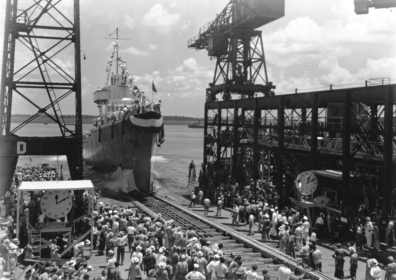On a bright, sunny day, Corry slides down the building ways at Charleston Navy Yard, 28 July 1941 to an enthusiastic send-off. Note children scrambling on the shaded platform at left, and the women picking their way across obstructions at lower left to catch a glimpse of the ship entering the river. (U.S. Navy Bureau of Ships Photograph 19-LCM Collection, National Archives and Records Administration, Still Pictures Division, College Park, Md.)
