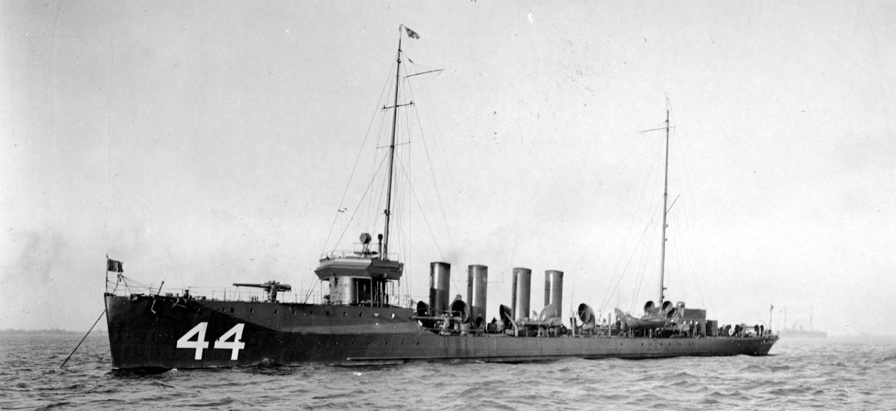 "Cummings, her division number (a script ""6"") displayed on her no. 2 stack, lies anchored in Hampton Roads, circa December 1916. (U.S. Navy Bureau of Ships Photograph 19-N-1745, National Archives and Records Administration, Still Pictures Branch, College Park, Md.)"