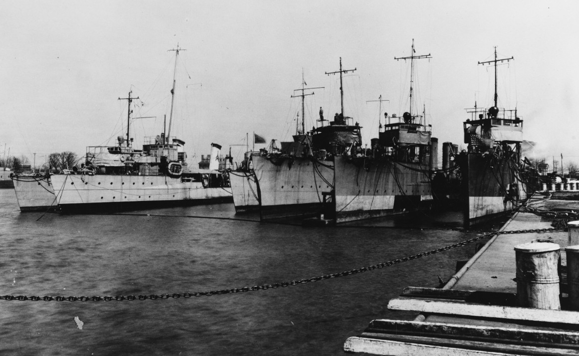 "Destroyers in the Philadelphia Navy Yard's Reserve Basin awaiting decommissioning, circa March-April 1919. Ships present include (from left to right): Preble (Destroyer No. 12); Decatur; Paul Jones (Destroyer No. 10); an unidentified 750-ton ""flivver"" destroyer; Flusser (Destroyer No. 20); and another unidentified 750-ton destroyer. Note the bent bow on the third ship from right. (Naval History and Heritage Command Photograph NH 43037)"