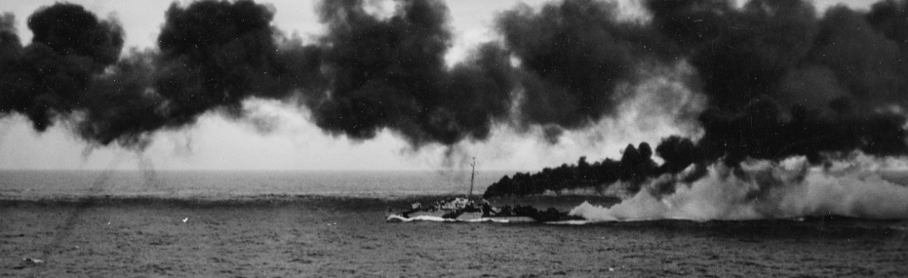 Dennis lays funnel (black) and chemical (white) smoke during the Battle off Samar, 25 October 1944, in this considerably enlarged image captured by a photographer on board the escort carrier Kitkun Bay (CVE-71). (U.S. Navy Photograph 80-G-287459, National Archives and Records Administration, Still Pictures Division, College Park, Md.)