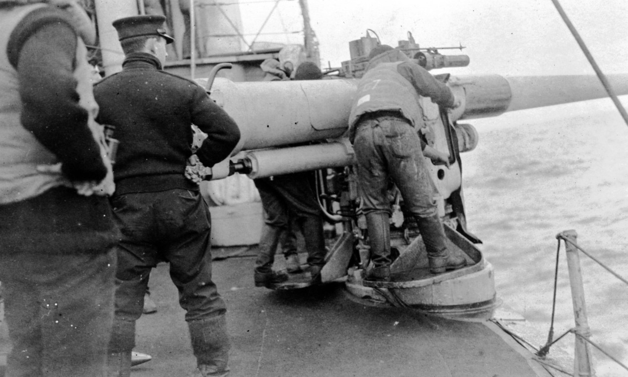 "Lt. Cmdr. Buchanan, commanding officer of Downes, oversees target practice outside of Queenstown (Base Six) with one of the 4-inch waist guns. The men are dressed comfortably, if rather informally, for duty at sea, with the boots donated to the crew by a Mrs. Tucker of Boston. ""Dexterity in handling the controls of unprotected gun mounts and torpedo tubes in the Atlantic weather,"" one observer wrote, ""seems to have been a matter of adequate clothing, plenty of training and a good amount of determination."" (Naval History and Heritage Command Archives, Ships History-Decommissioned, Box 247, Downes (Destroyer No. 45) file)"
