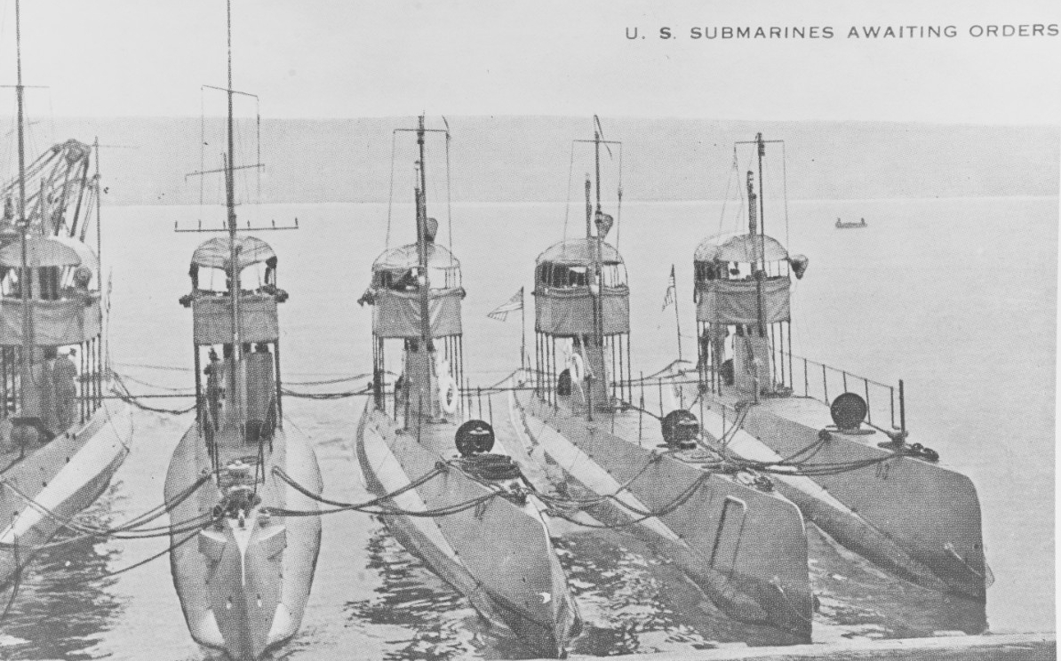 U.S. submarines awaiting orders. Halftone reproduction, printed on a postal card, of a photograph of five submarines nested together prior to World War I. The three boats at right are (from center to right): D-2 (Submarine No. 18); D-1 (Submarine No. 17); and D-3 (Submarine No. 19). The two at left are probably (in no particular order) E-1 and E-2 (Submarine No. 25). (Naval History and Heritage Command Photograph NH 78926)