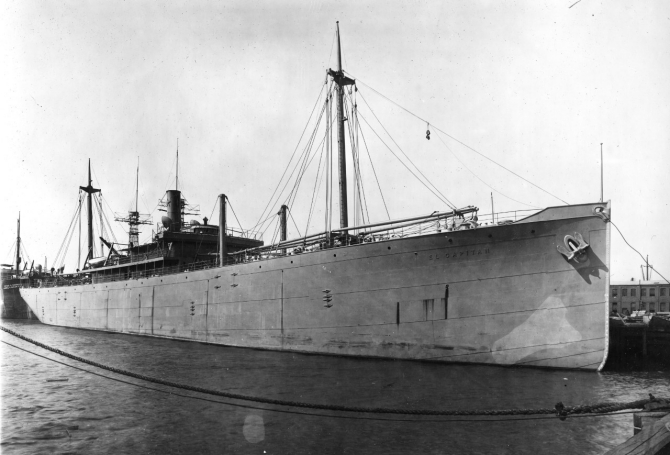 El Capitan, circa 1917, her name in raised letters on her bow, probably photographed at her building yard. Steamship Peter H. Crowell, moored astern, later served in the U.S. Navy, given the classification Id. No. 2987, and was commissioned on 20 December 1917. Note how El Capitan is riding high out of the water; she is drawing about 7 feet at this time. Also note the battleship masts in the background, visible beyond the freighter's funnel. (19-LCM Collection, Box 615, National Archives and Records Administration, Still Pictures Branch, College Park, Md.).