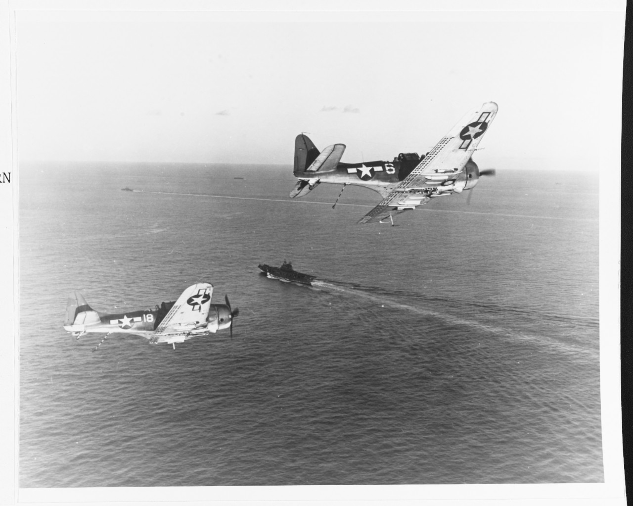 A pair of SBD-5s of VB-20 lower their tail hooks and turn into the landing pattern while returning to the ship after bombing the Japanese in Palau, March 1944. (U.S. Navy Photograph 80-G-251061, National Archives and Records Administration, Still Pictures Branch, College Park, Md.)