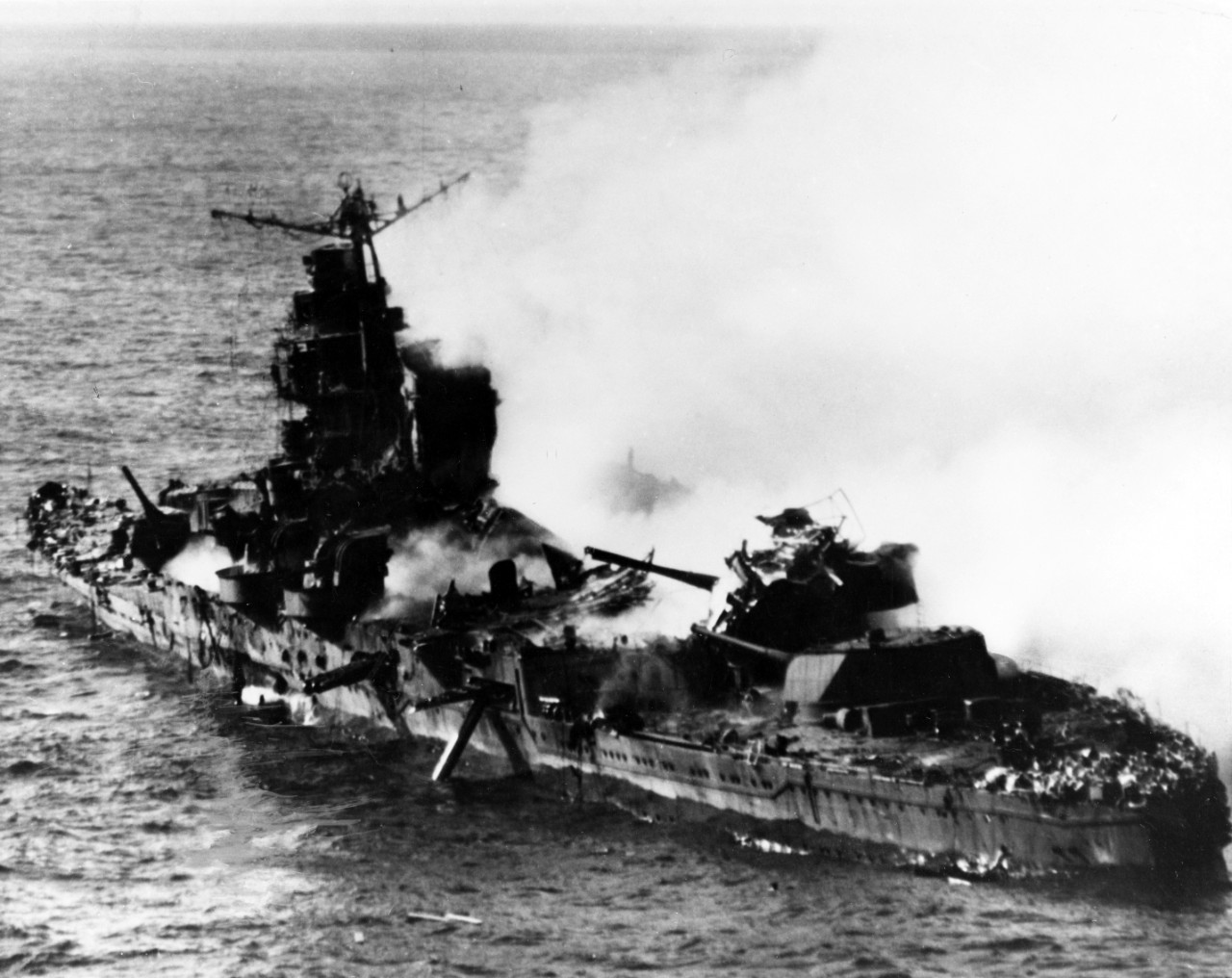 This close up picture shows the devastated ship in more detail. Her midships structure lies shattered, and both portside torpedo tubes are trained outboard. Parts of the aft superstructure, and possibly the mainmast, collapse across her No. 4 8-inch gun turret — the wreckage does not comprise Capt. Fleming's Vindicator, which crashes into the sea. (U.S. Navy Photograph 80-G-414422, National Archives and Records Administration, Still Pictures Section, College Park, Md.)