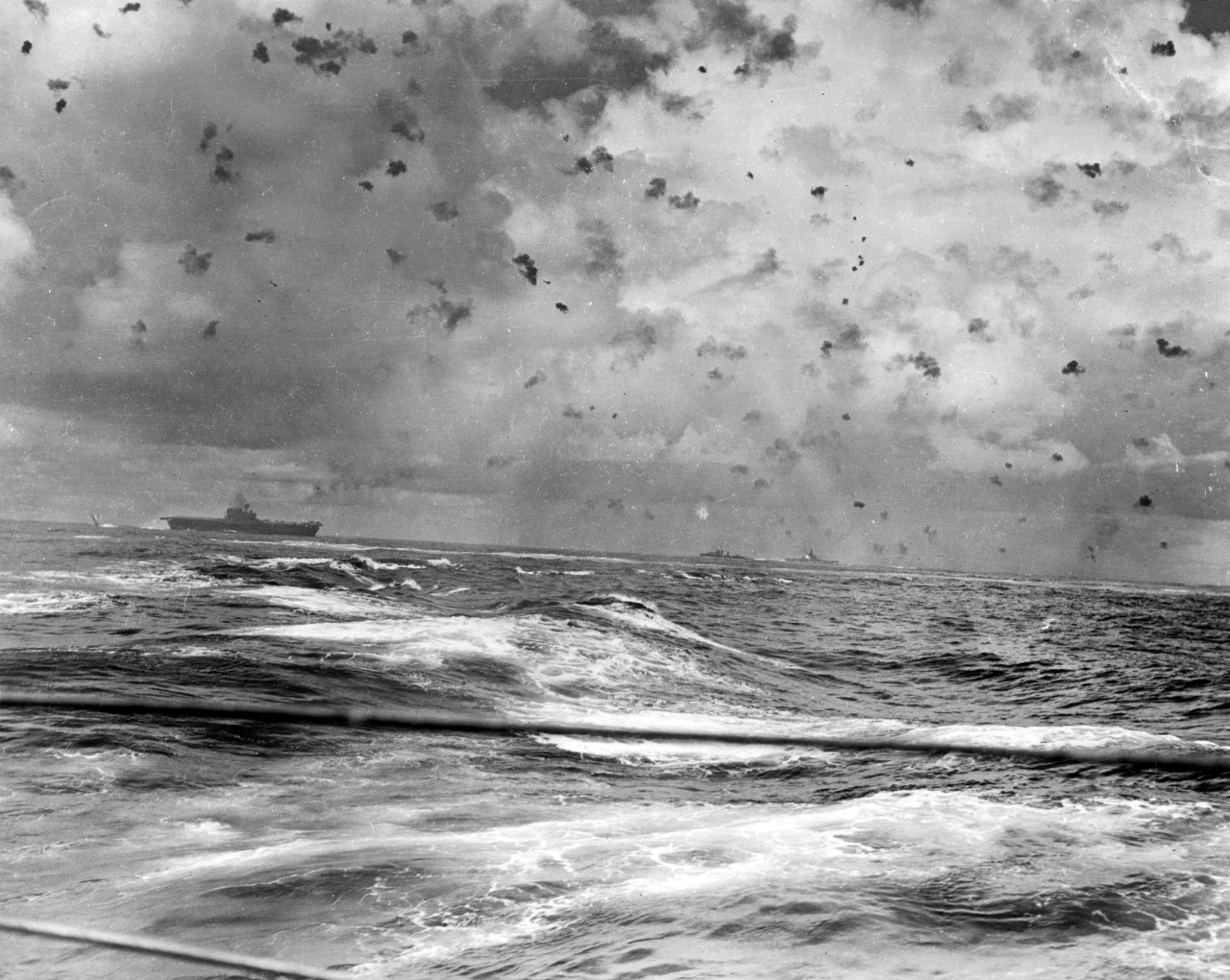 Antiaircraft gunners desperately fill the sky with flak and ships churn the water as they maneuver at speed and fight off the Japanese attackers, 26 October 1942. At least two enemy planes are visible above Enterprise, and the blast of South Dakota's starboard 5-inch guns mark the ship (right center). (U.S. Navy Photograph 80-G-20989, National Archives and Records Administration, Still Pictures Branch, College Park, Md.)