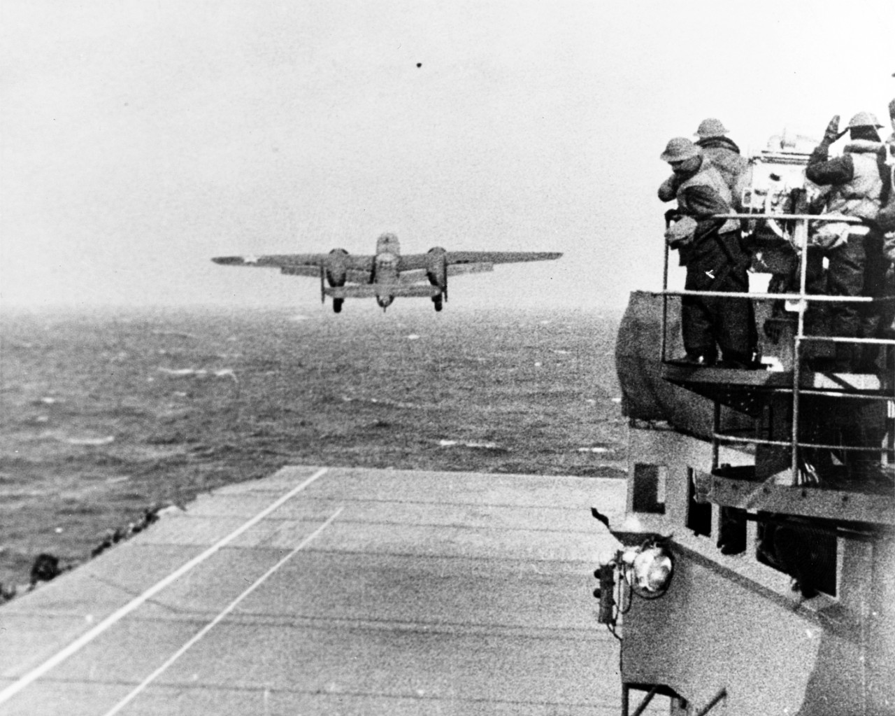 A B-25B Mitchell of the Army's 17th Bombardment Group takes off from Hornet to bomb the Japanese home islands, 18 April 1942. Note the men wearing the old British style M1917A1 helmets as they watch from the signal lamp platform (right). (U.S. Navy Photograph 80-G-41196, National Archives and Records Administration, Still Pictures Branch, College Park, Md.)
