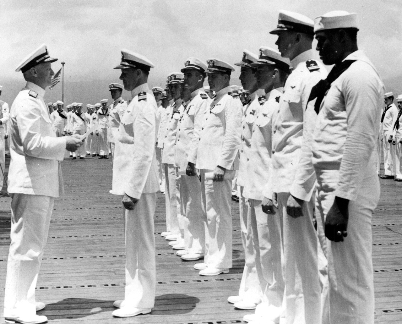 Adm. Nimitz awards Lt. Cmdr. McClusky the Distinguished Flying Cross during a ceremony on the flight deck of Enterprise at Pearl Harbor, 26 May 1942. MATT2c Doris Miller, who receives the Navy Cross for his valorous actions during the Japanese attack on 7 December 1941, also stands in the ranks (right foreground). (U.S. Navy Photograph 80-G-23590, National Archives and Records Administration, Still Pictures Branch, College Park, Md.)