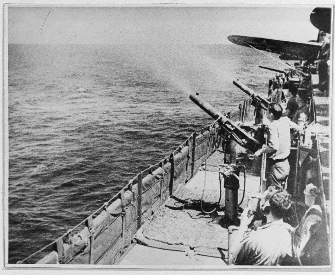 Crewmen practice firing .50 caliber machine guns, early 1942. The wing of a Dauntless is visible (right). (Naval History and Heritage Command Photograph NH 50935)