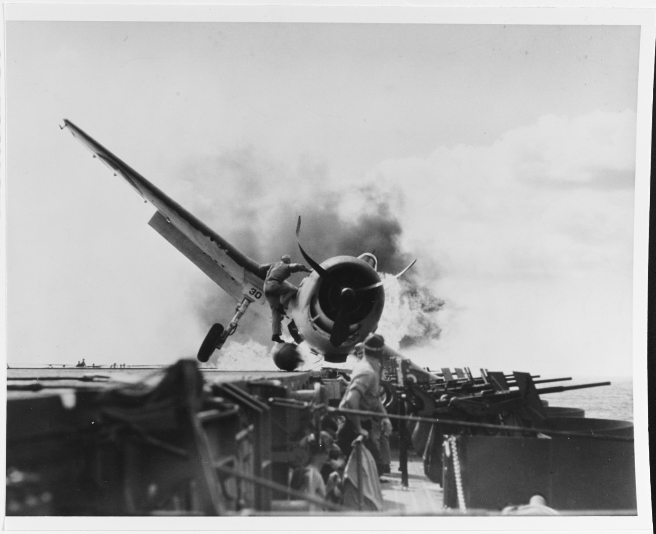 An F6F-3 of VF-2, Ens. Byron M. Johnson, crashes into the ship's port 20 millimeter gun gallery while landing and the Hellcat's belly fuel tank erupts into flames, 10 November 1943. Lt. Walter L. Chewning Jr., USNR, the catapult officer, scrambles onto the burning Hellcat to pull Johnson from the fire. (U.S. Navy Photograph 80-G-205473, National Archives and Records Administration, Still Pictures Branch, College Park, Md.)
