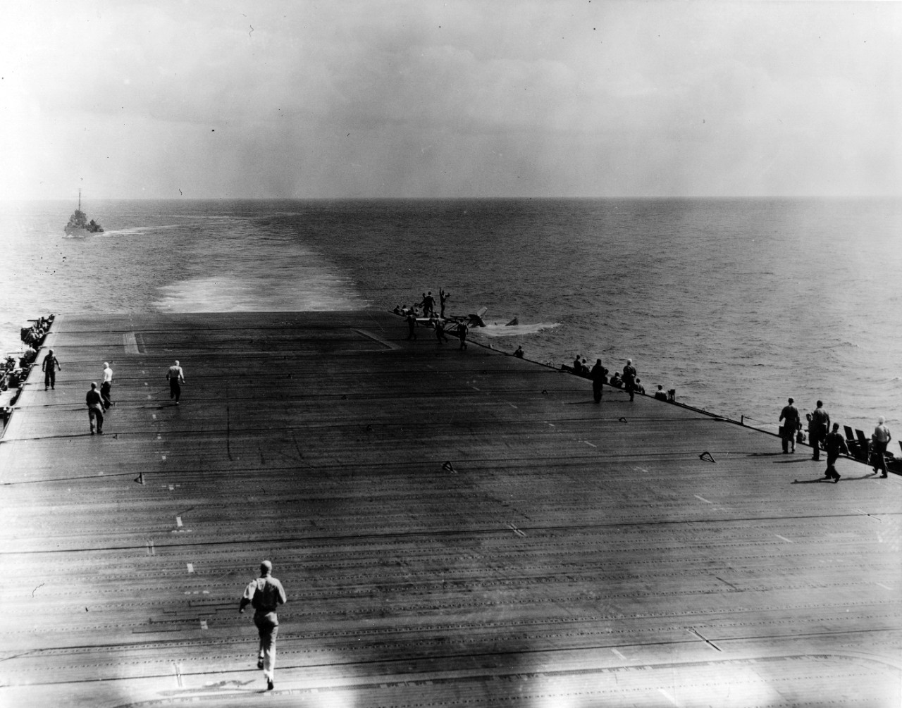 Lt. Cmdr. Eugene E. Lindsey's Douglas TBD-1 Devastator (BuNo. 0370) sinks astern of Enterprise after a deck landing accident, 28 May 1942. Monaghan steams as the plane guard destroyer in the left background, and rescues Lindsey and his crew. Enterprise is en route to the Battle of Midway, and Lindsey is the commanding officer of VT-6, who flies out with the rest of the air group to join the ship when he crashes. (U.S. Navy Photograph 80-G-7744, National Archives and Records Administration, Still Pictures Branch, College Park, Md.)