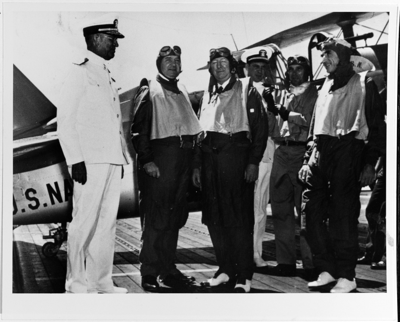 Secretary of the Navy Frank Knox (center) prepares for his flight from Enterprise to NAS Pearl Harbor, 13 September 1940. Additional men in the picture include: Adm. Richardson (left); Cmdr. Morton L. Deyo; and Lt. Cmdr. Edward C. Ewen, Enterprise Air Group Commander (left of Deyo and putting his gloves on). The men stand before an SBC-4 (most likely BuNo. 1295). (Naval History and Heritage Command Photograph NH 50281)