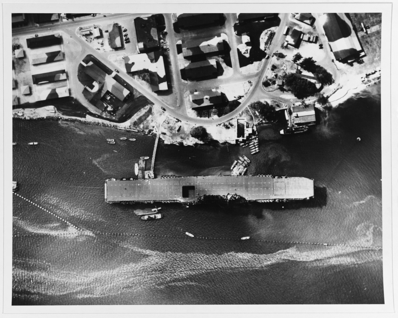 A plane captures this overhead view of the ship moored at Ford Island, 12 July 1942. Note the Wildcat on the barge alongside aft, the antitorpedo nets, and the camouflaged buildings on the island. (Naval History and Heritage Command Photograph NH 83990)