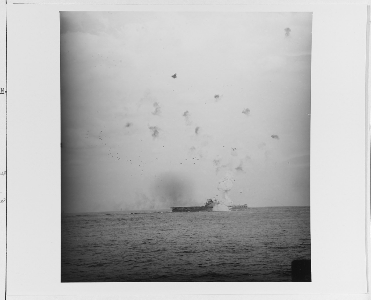 Despite the intense flak bursts over Enterprise the Zeke slams into the ship to starboard, as seen from Bataan (CVL-29), 13 May 1945. A huge column of smoke rises from the carrier, and she has way on in the midst of an emergency turn. (U.S. Navy Photograph 80-G-323565, National Archives and Records Administration, Still Pictures Branch, College Park, Md.)
