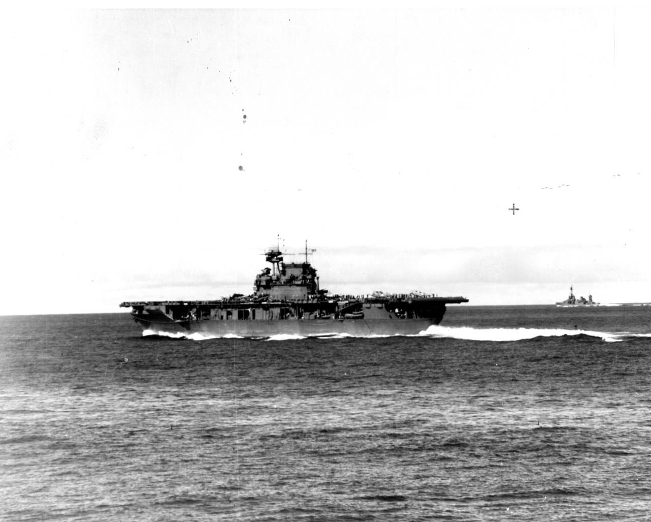 A sailor on board Pensacola snaps this picture of Enterprise as she steams at high speed during the Battle of Midway, at about 0725 on 4 June 1942. The carrier has just launched Dauntlesses of VB-6 and VS-6, and is striking her unlaunched bombers below to prepare to launch Wildcats of VF-6 and Devastators of VT-6. Some SBDs orbit overhead while they await the launch of additional planes, and Northampton (far right) faithfully shepherds Enterprise. (U.S. Navy Photograph 80-G-32225, National Archives and Records Administration, Still Pictures Branch, College Park, Md.)