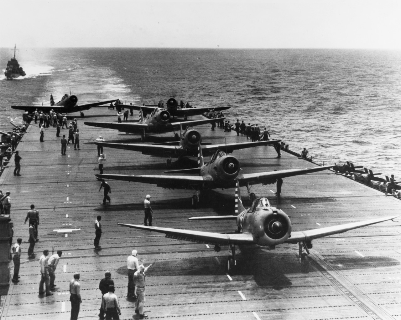 An SBD Dauntless and five TBD-1 Devastators of VT-6 prepare to take off from the ship as she steams southward through a calm sea, 4 May 1942. The launching officer signals the pilots by hand (lower left). (U.S. Navy Photograph 80-G-10151, National Archives and Records Administration, Still Pictures Branch, College Park, Md.)