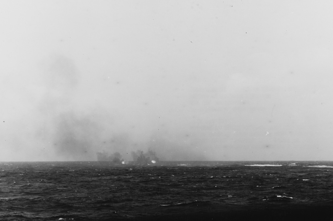 Nashville fires her 6-inch guns at one of the enemy picket boats, 18 April 1942. Photographed from Salt Lake City. (Naval History and Heritage Command Photograph NH 97500)