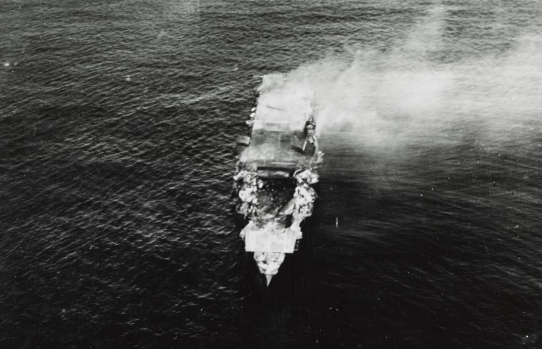 A plane flying from Hōshō takes this picture of Hiryū as she smolders shortly after sunrise, 5 June 1942. The exploding U.S. bombs have collapsed her flight deck over the forward hangar, and the ship will sink in a few hours. (Donated by Kazutoshi Hando, 1970, Naval History and Heritage Command Photograph NH 73065)