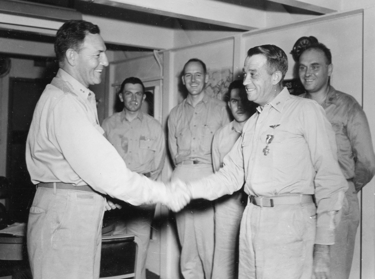 On board Fanshaw Bay, 15 March 1945, Rear Adm. Calvin T. Durgin awards Rear Adm. Clifton Sprague the Navy Cross, honoring the latter's heroic leadership of Taffy 3 off Samar on 25 October 1944. (U.S. Navy Photograph 80-G-364246, National Archives and Records Administration, Still Pictures Division, College Park, Md.)