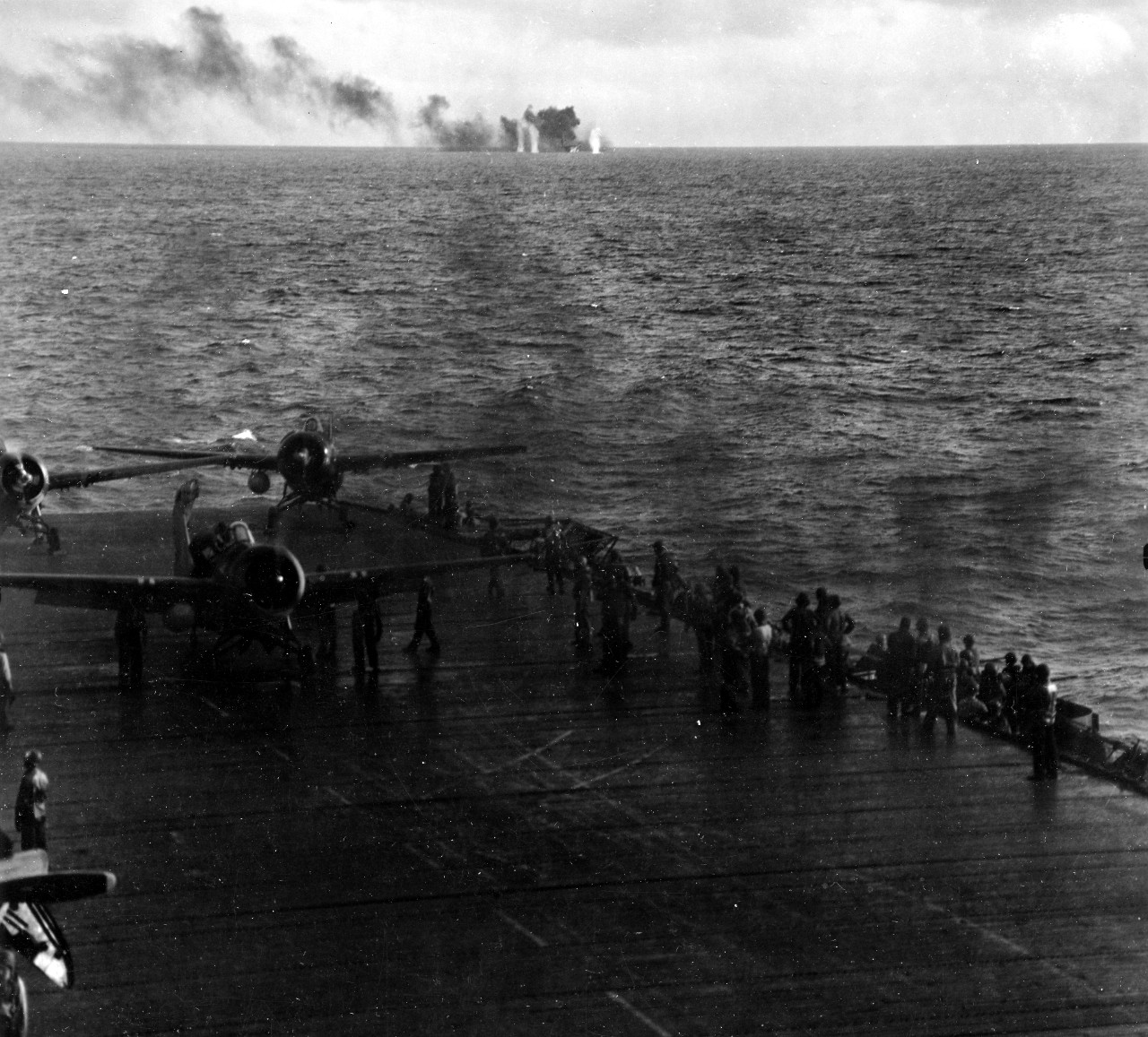 In this chilling image captured by a photographer on board sister ship Kitkun Bay, Fanshaw Bay is straddled by shells from a Japanese battleship (either Kongo or Haruna) off Samar, 25 October 1944, while purposeful activity proceeds ahead on the flight deck in the foreground, with three FM-2s being prepared for launching. (U.S. Navy Photograph 80-G-287492, National Archives and Records Administration, Still Pictures Division, College Park, Md.)