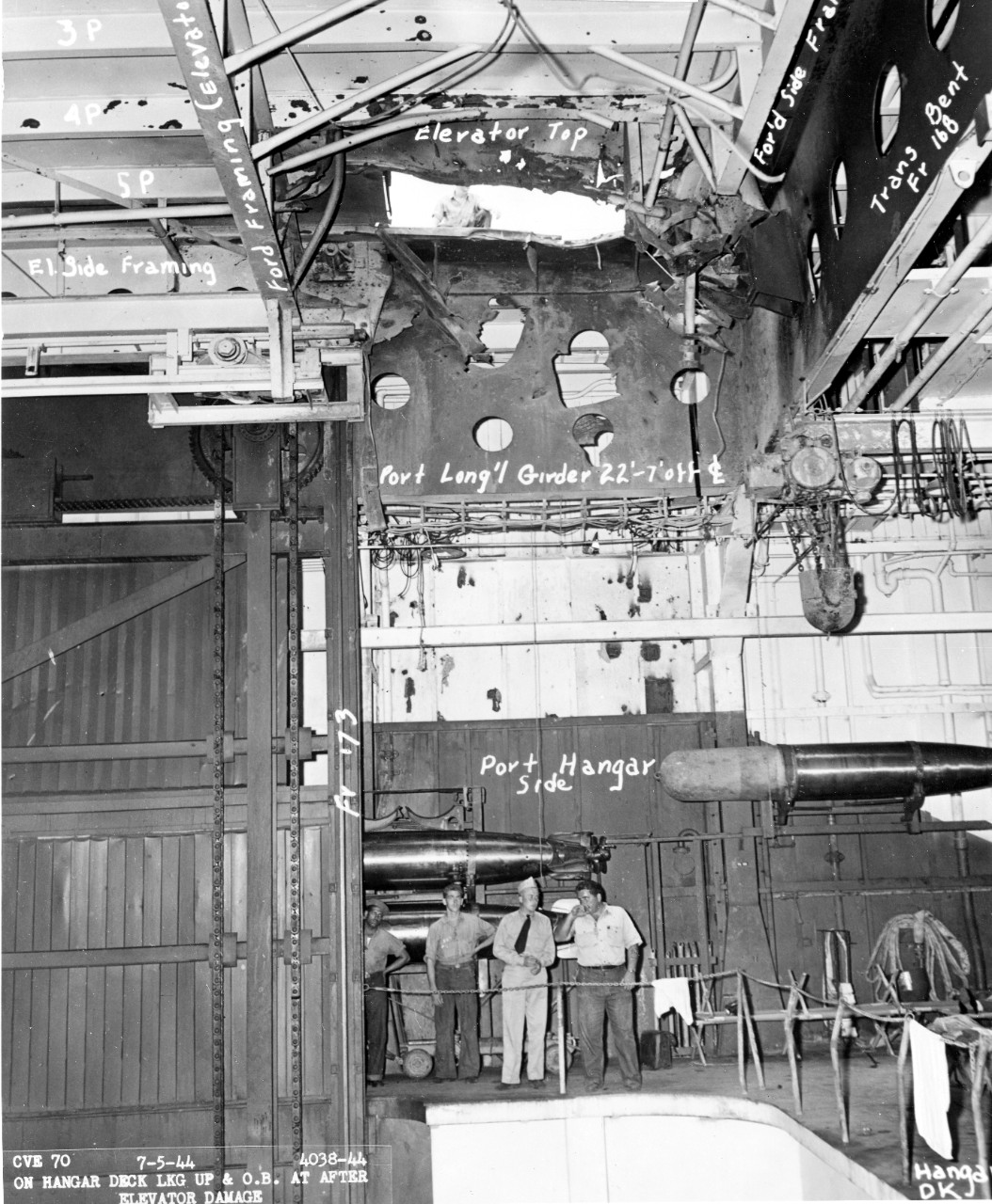 Fanshaw Bay at Pearl Harbor Navy Yard, 5 July 1944, showing a hole in the elevator (top) from a Japanese bomb. Note the size when compared to the man seen on the flight deck, and the size of the men on the hangar deck involved in inspecting the damage. Note the torpedo stowage. (U.S. Navy Bureau of Ships Photograph BS-110053, National Archives and Records Administration, Still Pictures Division, College Park, Md.)
