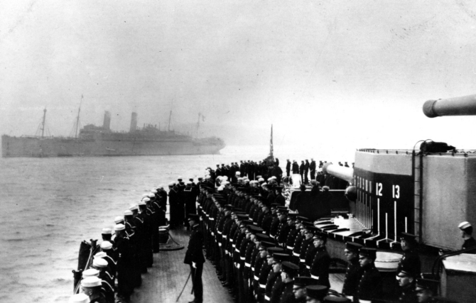 Ship's crew manning the rail as George Washington (in background) enters Brest harbor, France, with President Woodrow Wilson on board, 13 December 1918. Note marines in the center foreground, and bearing markings painted on her 12-inch gun turret side. (Collection of Adm. Montgomery M. Taylor, 1962, Naval History and Heritage Command Photograph NH 78103).