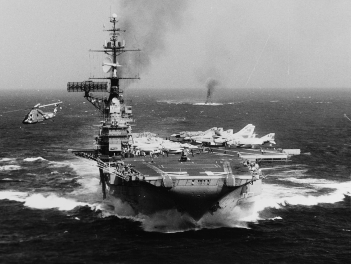 Franklin D. Roosevelt churns up the water as she steams in the South China Sea during the Vietnam War, 19 October 1966. One of her busy Seasprites lifts off and clears the ship to starboard, and the ubiquitous plane guard ship, a boon to pilots, sails astern. (PH1 Hendricks, Naval History and Heritage Command Photograph NH 1120428)