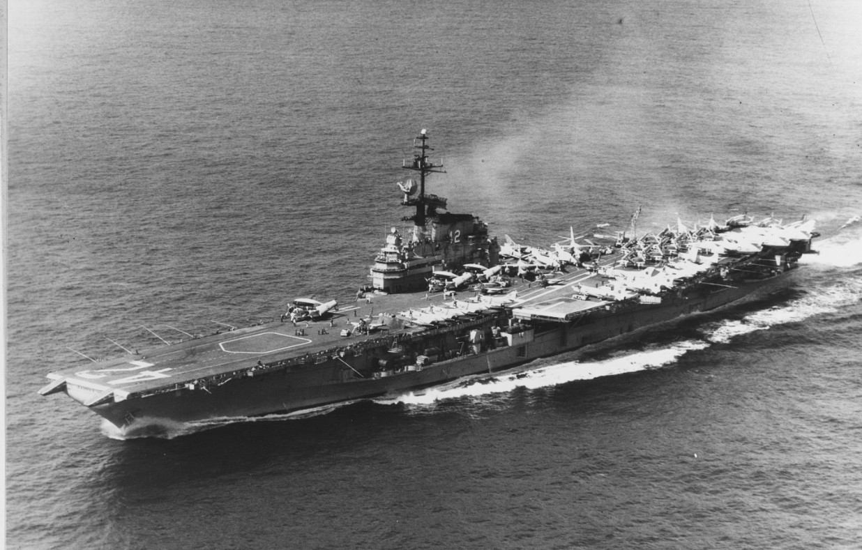An aerial photograph of the ship captures her slicing cleanly through a calm sea, most likely during her deployment to the Vietnam War, 1966–1967. The Phantom IIs parked on the flight deck sport AB tail codes, identifying them as serving in CVW-1, and all three of the embarked E-1B Tracers are visible on the starboard side. (Naval History and Heritage Command Photograph NH 82283)