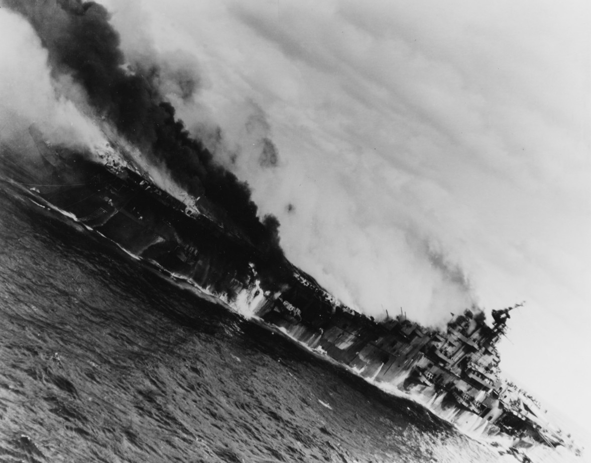 Franklin burning and down by the stern after being hit by two 550-pound Japanese semi-armor piercing bombs on 19 March 1945. (U.S. Navy Photograph 80-G-273867, National Archives and Records Administration, Still Pictures Division, College Park, Md.)