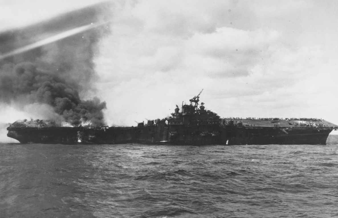Franklin on fire and listing following the attack on 19 March 1945. Note what appears to be the towing wire from Pittsburgh (CA-72) attached to the outboard end of the carrier's starboard anchor chain. Photographed from Santa Fe. (U.S. Navy Photograph 80-G-273894, National Archives and Records Administration, Still Pictures Division, College Park, Md.)
