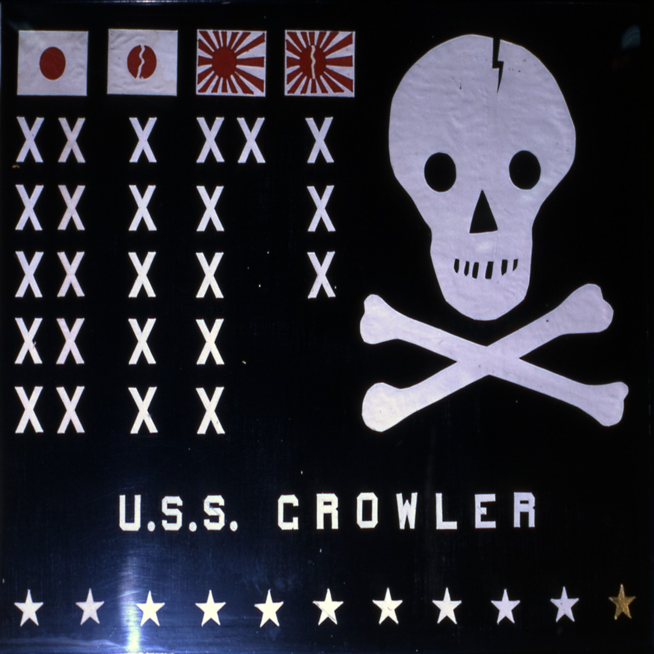 Battle flag of Growler depicts the enemy ships she had sunk as well as her eleven war patrols, with the gold star indicating she was on eternal patrol. (Naval History and Heritage Command Photograph UA 80.01.01)