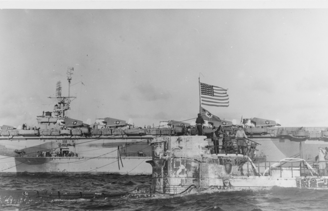 The U.S. flag flies over the German naval ensign from U-505's periscope, which the boarders use as a jackstaff, 6 June 1944. This picture shows the submarine two days after her capture, and American sailors run hoses over the side to drain the water from her. Guadalcanal is in the background, with several Avengers parked on her flight deck. (U.S. Navy Photograph 80-G-324800, National Archives and Records Administration, Still Pictures Division, College Park, Md.)
