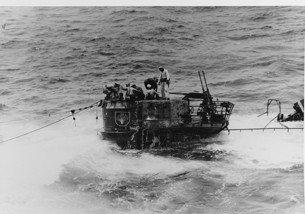 Men of the salvage party use a small handy-billy pump to dewater the boat. U-505's freeboard is dangerously low as she settles, with only some of her fairwater above the surface. Note the twin 20 millimeter guns, and the seashell insignia on the fairwater's side. (U.S. Navy Photograph 80-G-49167, National Archives and Records Administration, Still Pictures Division, College Park, Md.)