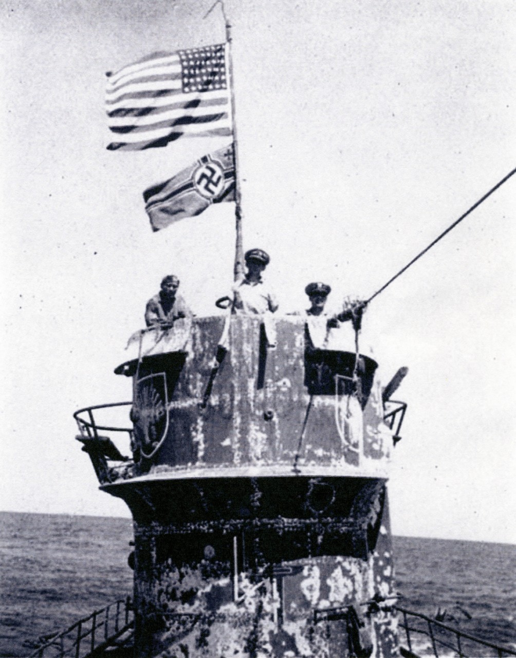A halftone reproduction of a photograph taken shortly after the boarders seized U-505, 4 June 1944. (Left–right) Lt. (j.g.) David, Capt. Gallery, and Cmdr. Trosino man the conning tower, as the Stars and Stripes flaps above the German naval ensign. The submarine's hull shows the wear of her long sojourn at sea. (Page 28, Guadalcanal (CVE-60) Memory Log, Ships History, Naval History and Heritage Command Photograph NH 105857)