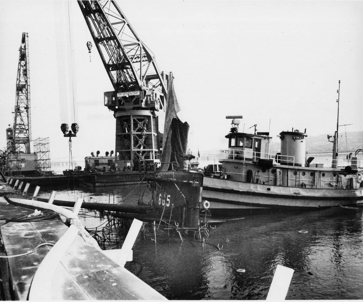 Guitarro after her sinking at Mare Island Naval Shipyard, Calif., showing medium harbor tug Satanta (YTM-270) positioned against the boat's sail to prevent her from capsizing. (U.S. Navy Photo No. MSA 91770-5-69)