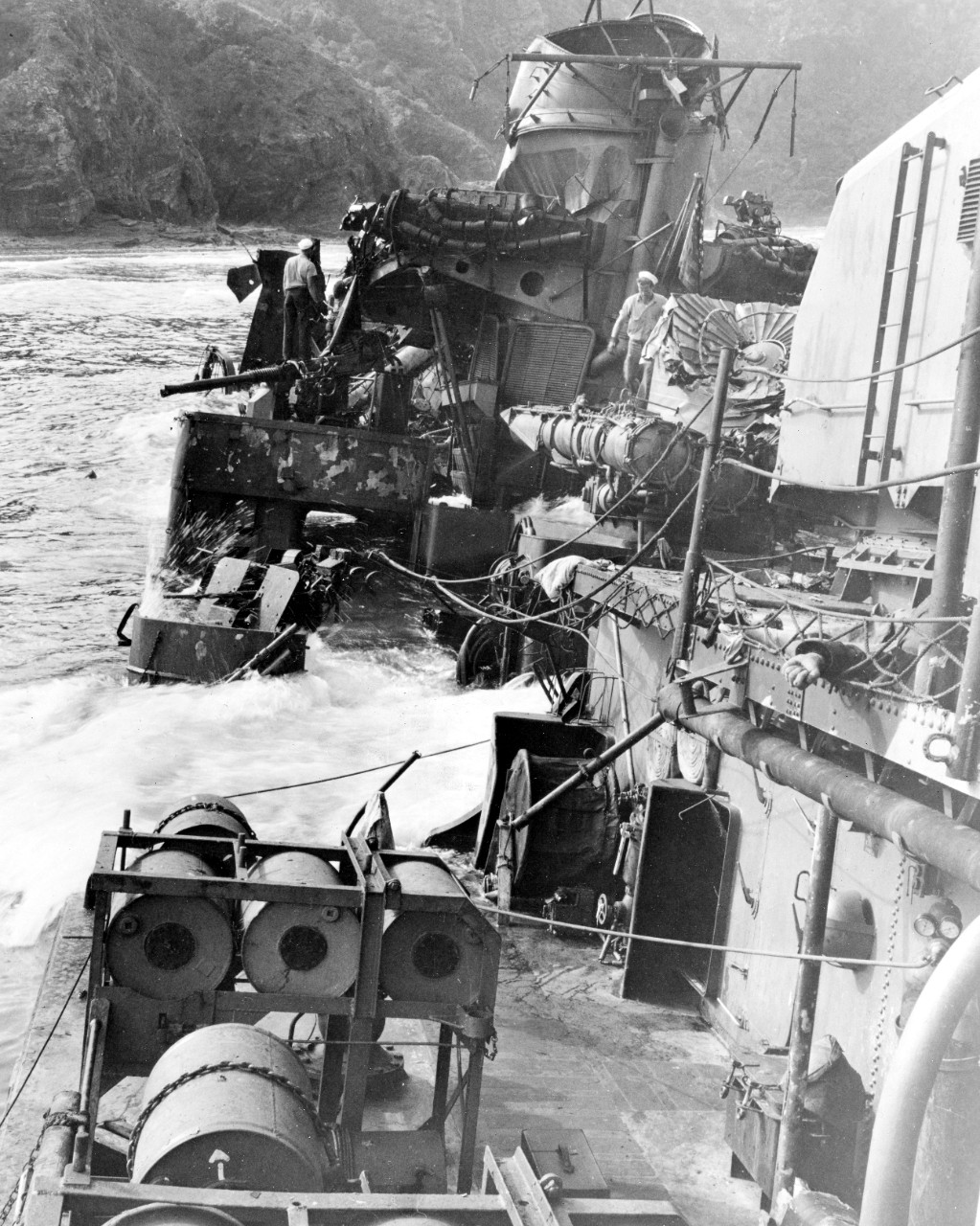 Taken by a member of the inspection party that visited Halligan's wreck on 28 March 1945, this photo shows the ship down by the bow, the surf breaking over the main deck on the port side, while very little forward of the No. 2 stack (her steaming colors hang limply from the gaff) resembled what had once been a trim destroyer. Note the conical shield for the No.2 torpedo tube has been smashed flat, and that evidently human remains are still on board, as a man's arm lies over the deck edge near Mount 53, clenched fist clearly visible. (U.S. Navy Photograph 80-G-324188, National Archives and Records Administration, Still Pictures Division, College Park, Md.)