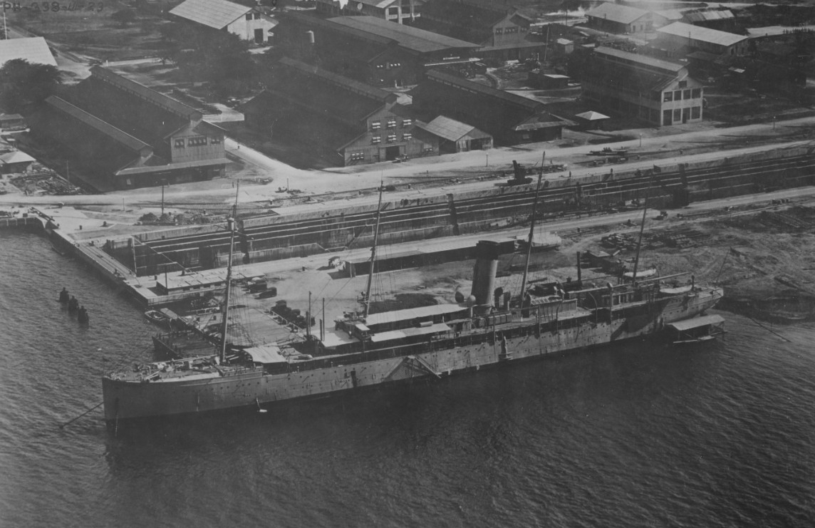 Hancock at the Pearl Harbor Navy Yard, 27 November 1923. She was then serving as the yard's Receiving Ship. Dry Dock No. 1 runs horizontally across the middle of the image. (Naval History and Heritage Command Photograph NH 104678)