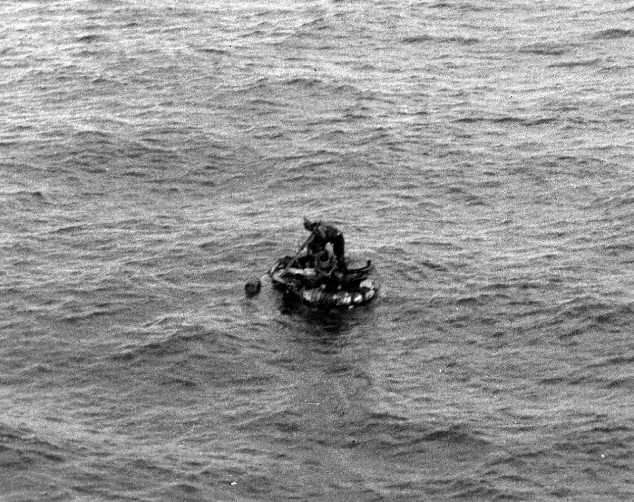 As first seen from Helm's bridge on 17 May 1942, one of the four survivors on a raft from the sunken oiler Neosho stands to attract attention. (U.S. Navy Photograph 80-G-32131, National Archives and Records Administration, Still Pictures Division, College Park, Md.)