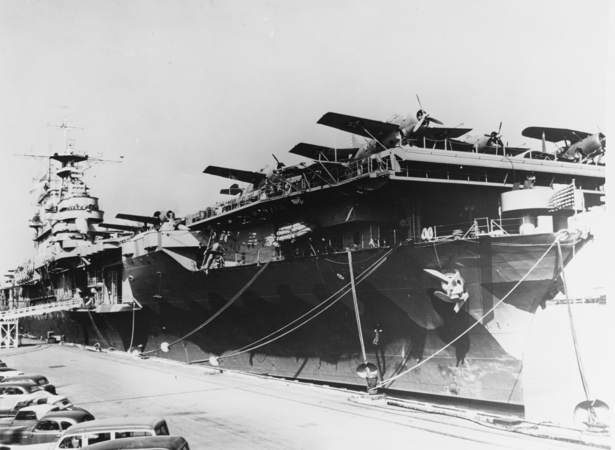 Hornet moors alongside Pier 7, NOB Norfolk, February 1942. The planes parked on the forward end of her flight deck (visible in the foreground) are Grumman F4F-4 Wildcats of VF-8 and Curtiss SBC-4s from either VB-8 or VS-8. Note the rat guards on the mooring lines. (U.S. Navy Photograph 19-N-28429, National Archives and Records Administration, Still Pictures Division, College Park, Md.)