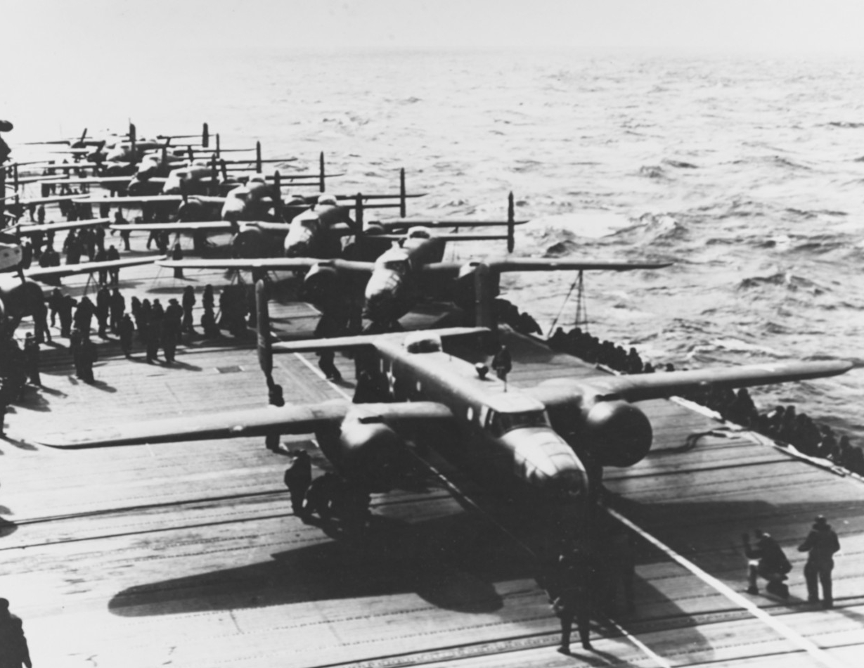 A Mitchell lines up as it prepares to take off to bomb the Japanese home islands, 18 April 1942. This is the 3rd or 4th plane to launch. Note the white lines on to the flight deck, below the bomber's nose and port side wheels, which guide the pilot during take off. (U.S. Navy Photograph NH 53420, Naval History and Heritage Command)