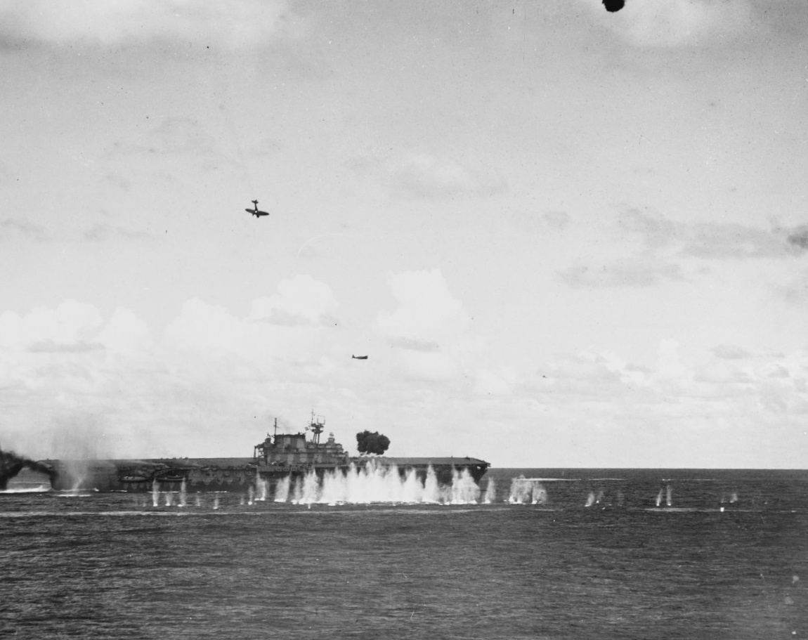 Japanese planes swamp Hornet's defenses at the Battle of the Santa Cruz Islands, 26 October 1942. An Aichi D3A1 Type 99 carrier bomber hit by U.S. fire trails smoke and hurtles toward the ship, and is about to smash into the carrier's stack and then her flight deck. An enemy Nakajima B5N2 Type 97 carrier attack plane flies over Hornet after dropping its torpedo, and another Type 99 attacks off her port bow. Antiaircraft rounds burst between Hornet and the camera, and their fragments strike the water nearby. (U.S. Navy Photograph 80-G-33947, National Archives and Records Administration, Still Pictures Division, College Park, Md.)