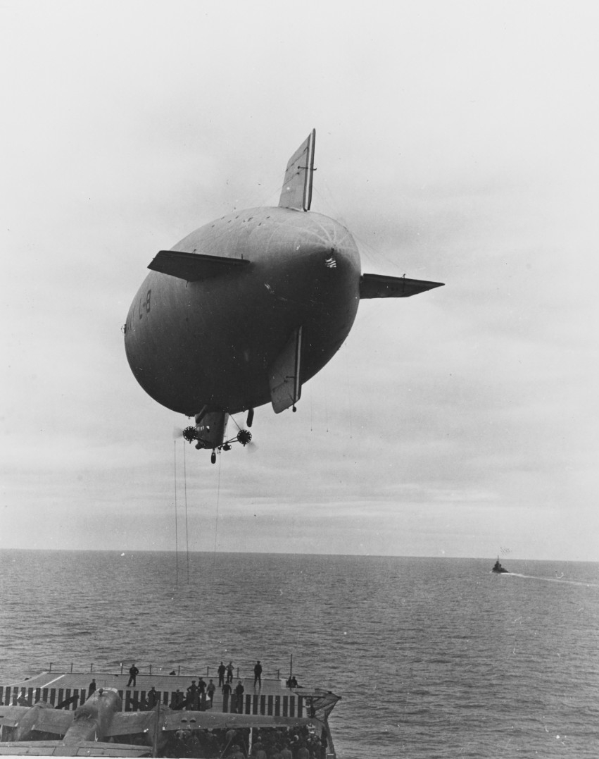 Navy blimp L-8 hovers over Hornet's flight deck as she delivers vital navigator's domes for the North American B-25B Mitchells, 2 April 1942. (U.S. Navy Photograph NH 53294, Naval History and Heritage Command)