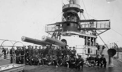 Sailors and marines of the ship's company pose in front of her forward 12-inch gun turret, circa August 1898. Note that Iowa has been partially repainted from her wartime gray. Brooklyn (Armored Cruiser No. 3) lies in the distance (R). (Naval History & Heritage Command Photograph NH 00087, original photograph by William H. Rau)